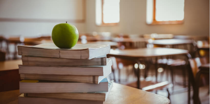 apple on top of books in classroom